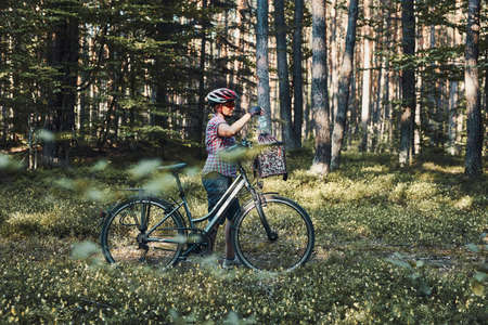 Active woman spending free vacation time on a bicycle trip in a forest on sunny summer day. Woman wearing bicycle helmet and gloves holding bike with basket standing behind the blurred tree leaves 版權商用圖片