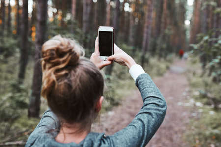 Young woman taking photos using smartphone during walk in a forest on summer vacation trip. Back view of girl holding smartphone 版權商用圖片