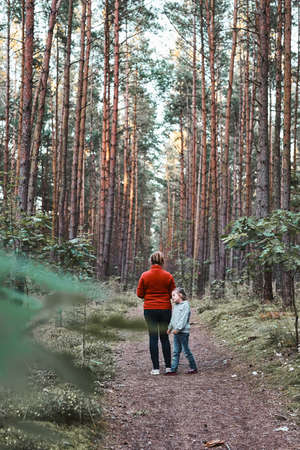 Mother and her little daughter walking in a forest during summer vacation trip. Family spending time together outdoors in nature