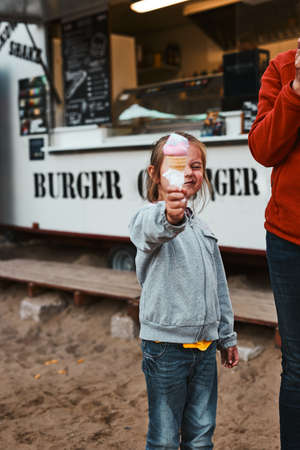 Little girl holding her ice cream in front of her face standing in front of food truck during summer vacations