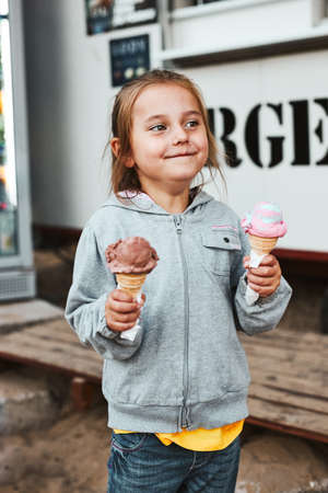 Happy smiling little girl holding two ice cream standing in front of food truck spending time on summer vacations