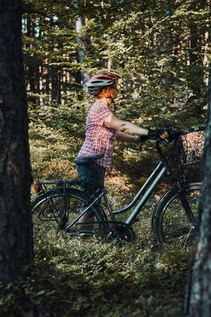 Active woman spending free summer vacation time on a bicycle trip in a forest. Woman wearing bicycle helmet and gloves holding bike with basket standing behind the trees 版權商用圖片