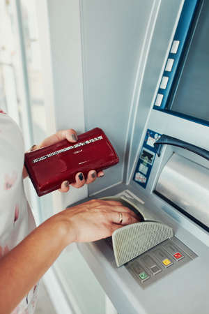 Woman withdrawing money from atm machine using debit or credit card using key pad on atm terminal