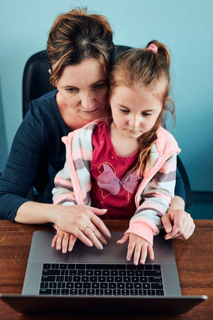 Little girl preschooler learning online solving puzzles playing educational games typing letters listetning to music and sounds with help of her mother using laptop computer and sitting at desk at home