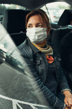 Woman sitting in a car wearing the face mask to avoid virus infection and to prevent the spread of disease in time of coronavirus