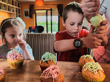 Group of children baking cupcakes, squeezing cream from confectionery bag, preparing ingredients, topping, sprinkles for decorating cookies. Kids cooking, working together in kitchen at home. Concept of happy family
