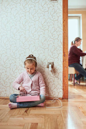 Little girl preschooler learning online solving puzzles playing educational games listetning to music and sounds using tablet and headpphones at home during pandemic quarantine