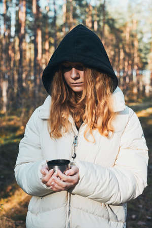 Woman in a hood having break during autumn trip holding cup with hot drink from flask on autumn cold day. Active girl wandering in a forest actively spending time Фото со стока