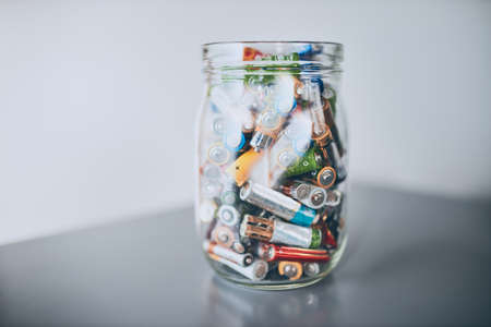 Jar filled with discharged used batteries. Waste disposal and recycling. Separating the waste. Batteries only container