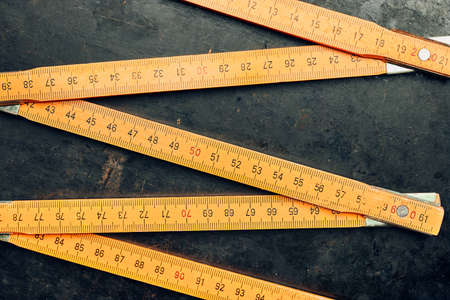 Wooden measure. Old ruler on metal surface. Measuring tool. Technical background with copy space