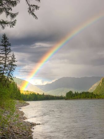 mountain stream: rainbow above river in mountains