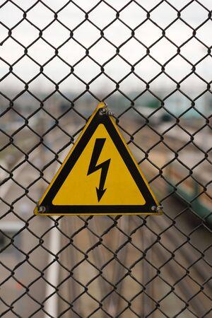 electricity danger sign on steel grid photo