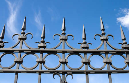 forge iron fence on blue sky