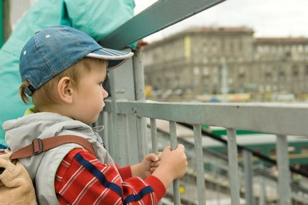 waif: sad baby looking from the bridge on railroad station