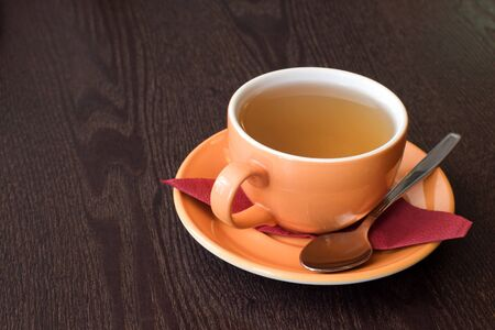 cup of tea on saucer with red napkin