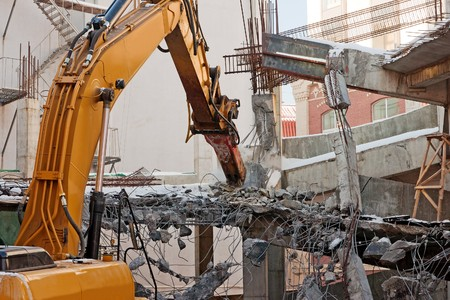 demolishing: heavy dredger is demolishing a house