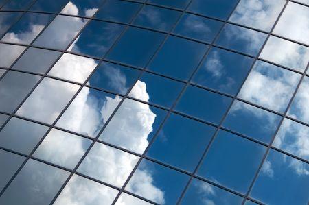 edificio cristal: edificio de oficinas con ventanas de espejo nubes Foto de archivo