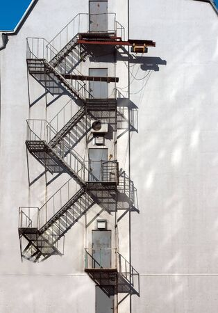 zigzag stairs on white building wall photo