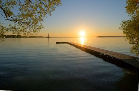 sunset over Volga river, wooden quay at foreground photo