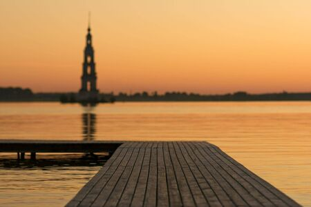 sunset over Volga river, wooden quay at foreground and chapel photo