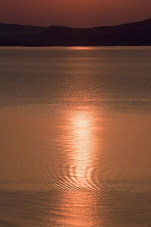 Morning on sea coast, red sun is relfected in water photo