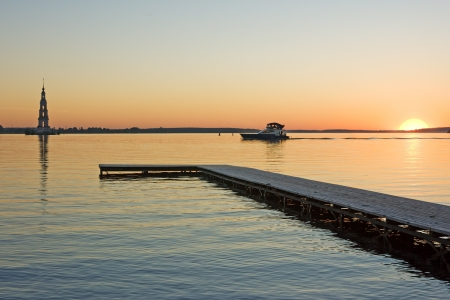 sunset over Volga river, wooden quay at foreground and boat photo