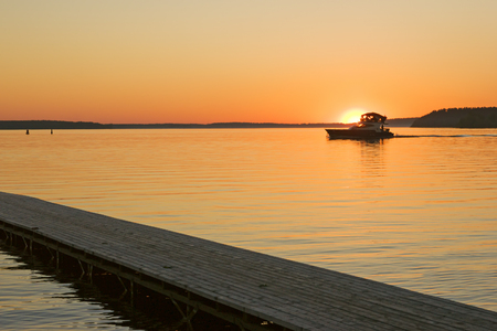 volga river: sunset over Volga river, wooden quay at foreground and boat