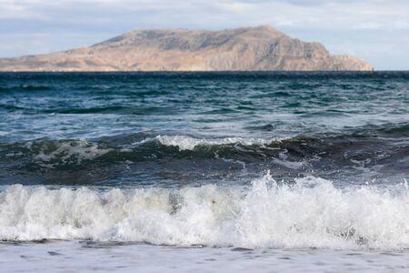 lejos: mar de surf con montañas lejanas en el fondo Foto de archivo