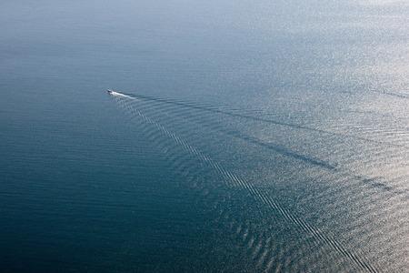 lejos: Barco rápido en el mar lejos azul
