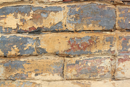 sidewall: Old brick wall with remnants of yellow and red paint