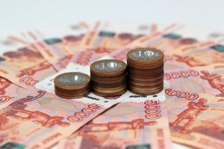 A stack of Russian commemorative ten-coins on background five-thousandth banknotes