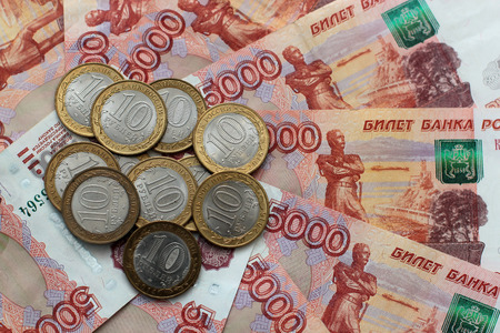 Russian money of five thousands denominations and commemorative coins lie on the table mixed