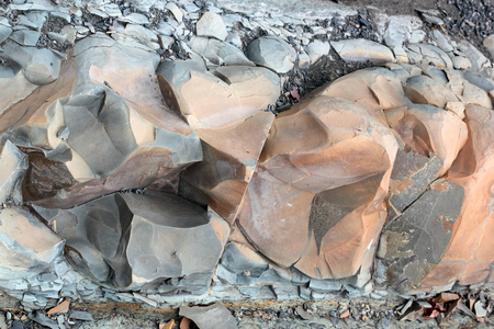 Cracks and colorful layers of sandstone background. A big heap of sandstones, storage space of various natural sandstone. The pattern of the variegated sandstones. Layers of toning colored big stones