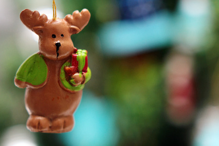 Christmas tree toy, Christmas deer with gift against Christmas tree. Christmas festive background