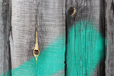 wooden fence with hole and green stripe