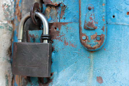 Old blue rustic door with rusty lock and keyhole