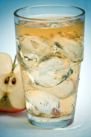 A glass of apple juice with ice cubes photo