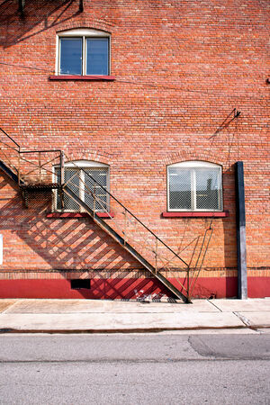 fire exit ladder with red brick building wall photo
