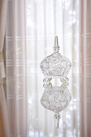 shinning light: oriental crystal glassware containers with white curtain Stock Photo