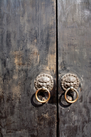 metal chinese door knockers with weathered wooden doors photo