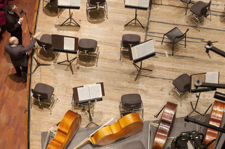 cellos: Stage viewed from above with empty chairs and cellos Stock Photo