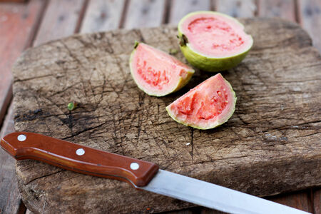 guava: Guava on old wooden chopping board