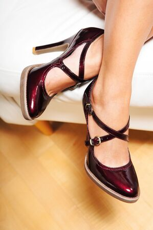 A womans legs in cherry red patent leather high heel shoes photo