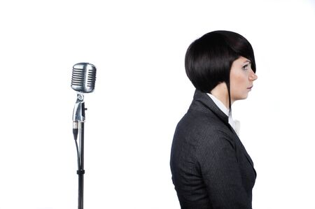 Young woman with fashion haircut sitting back to the vintage microphone, on white photo