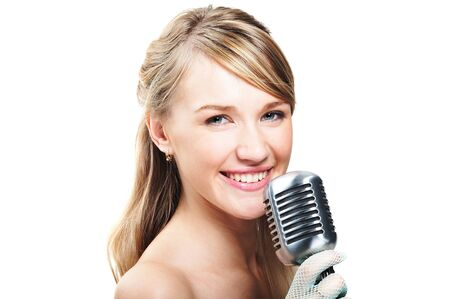 Pretty young girl singing into retro microphone, on white photo