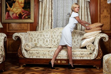 baroque room: Attractive maid making a sofa in luxury hotel Stock Photo