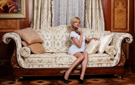 Flirting maid sitting on a sofa in luxury hotel Stock Photo - 4794481