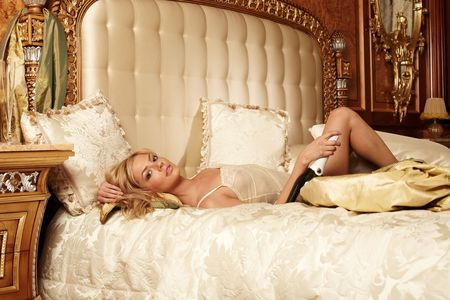 luxury hotel room: Young beautiful woman lying on a bed in a luxury hotel room