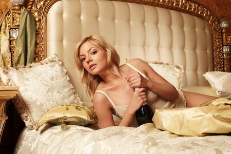 Young beautiful woman lying on a bed in a luxury hotel room Stock Photo - 5362098