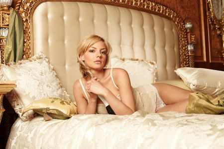 Young beautiful woman lying on a bed in a luxury hotel room photo
